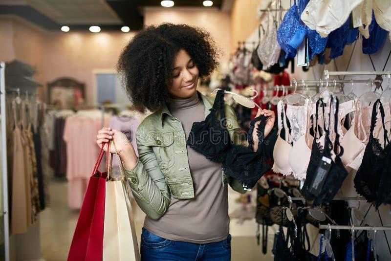 Jongelui die aantrekkelijke Afrikaanse Amerikaanse vrouw glimlachen die juiste bustehoudergrootte in de boutique van de lingerieo stock afbeeldingen