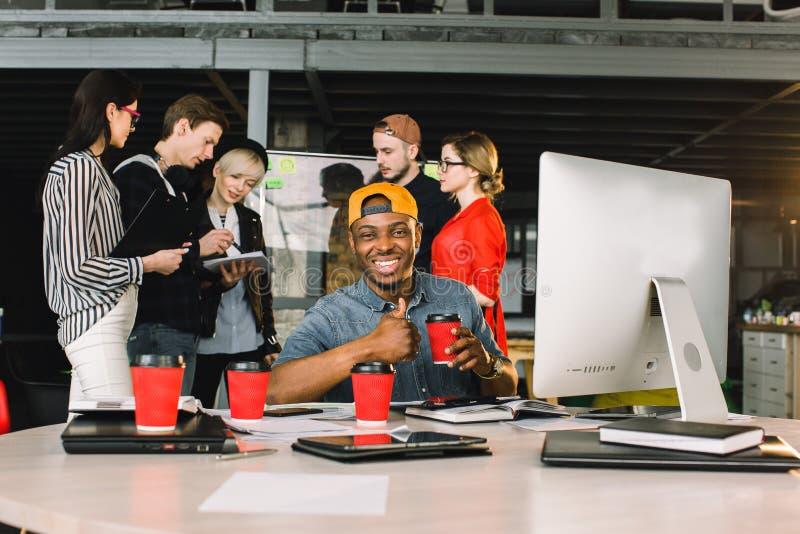 Jongelui die Afrikaanse Zakenman of freelancer in vrijetijdskleding met kop van koffie glimlachen, die Laptop met behulp van bij  royalty-vrije stock fotografie