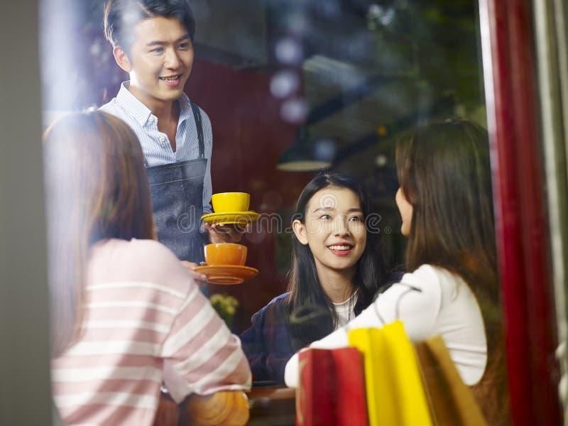 Jongelui die Aziatische kelners dienende koffie glimlachen aan klanten royalty-vrije stock foto