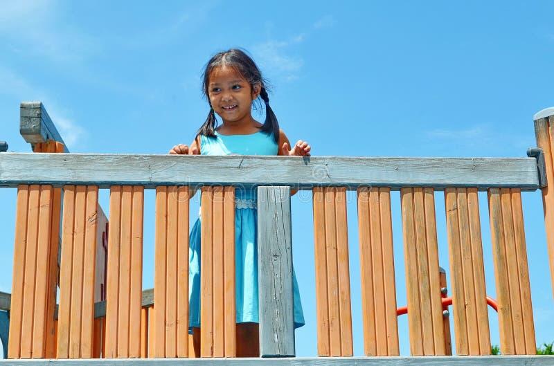 Jongelui die Aziatische meisje status op het materiaal van de gymnastiekspeelplaats glimlachen royalty-vrije stock afbeelding