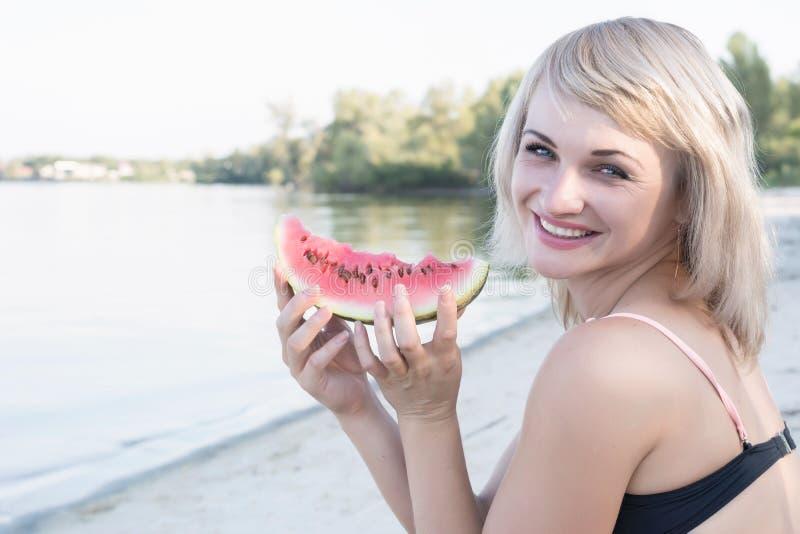 Jongelui die blonde vrouw met stuk van watermeloen glimlachen stock foto