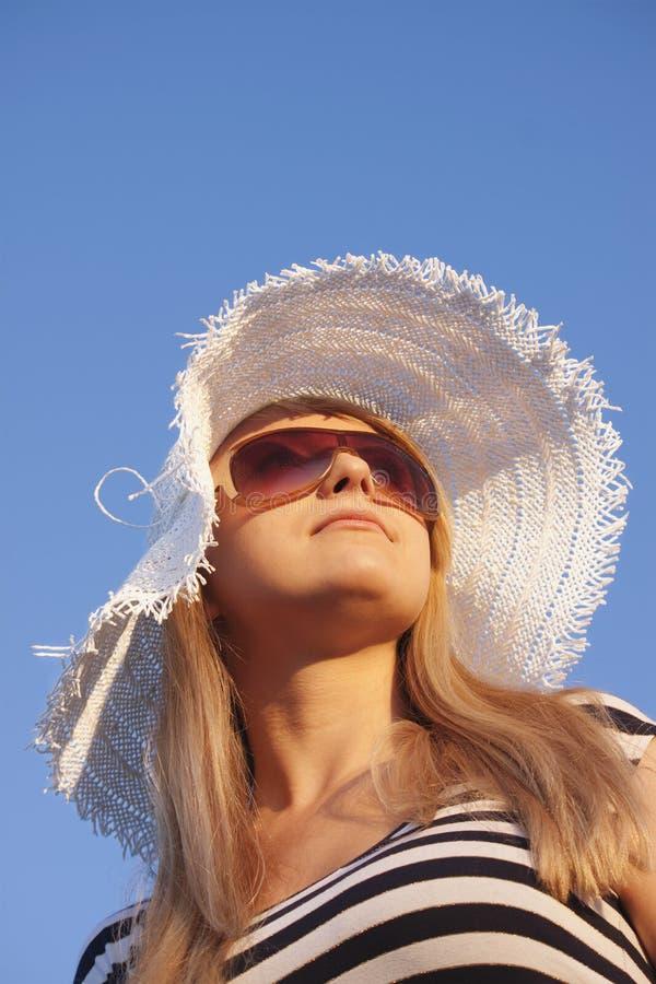 Jongelui die blonde vrouw met witte hoed glimlachen royalty-vrije stock foto's