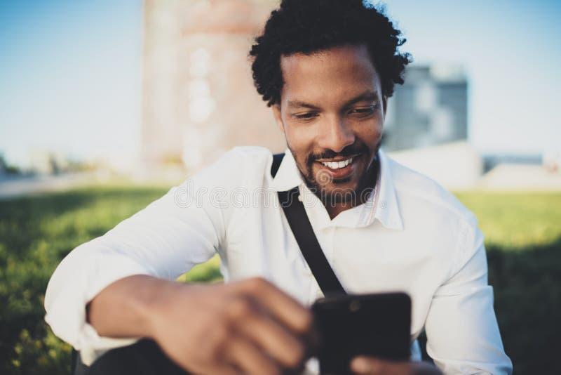 Jongelui die de Afrikaanse mens glimlachen die tekstbericht van smartphone verzenden terwijl het zitten bij zonnig stadspark Conc royalty-vrije stock afbeelding