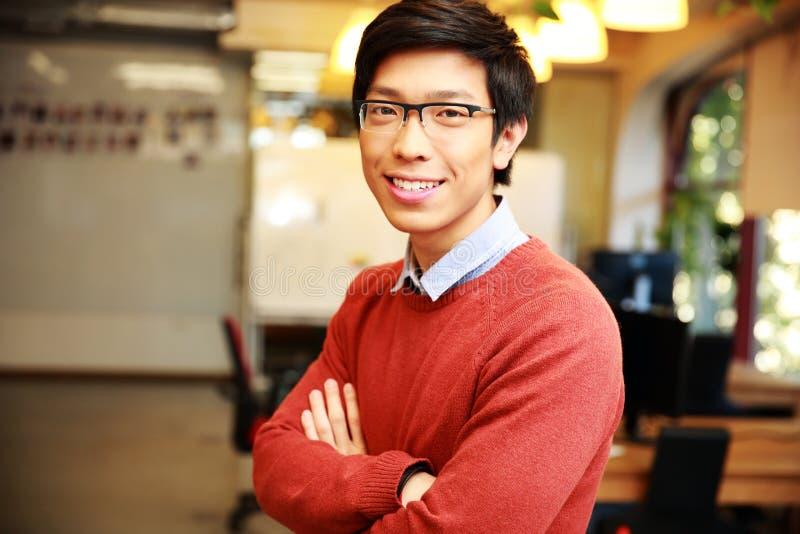 Jongelui die de Aziatische mens met gevouwen wapens glimlachen royalty-vrije stock afbeeldingen