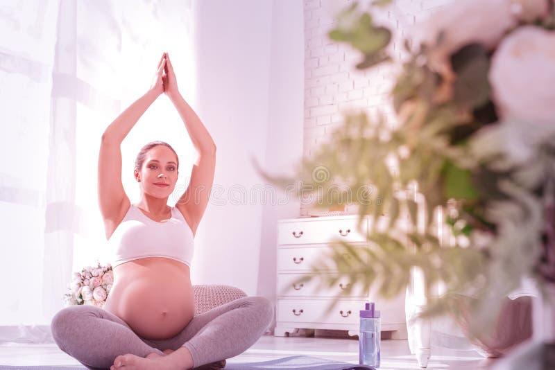 Jongelui die langharige zwangere vrouw in een witte t-shirt richten die vreedzaam kijken stock afbeeldingen