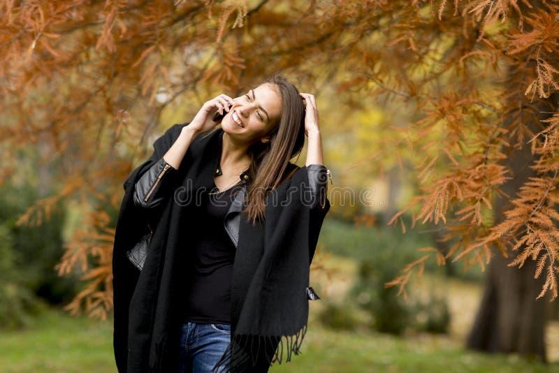 Jongelui die mobiele telefoon in de herfstpark womanusing stock afbeelding