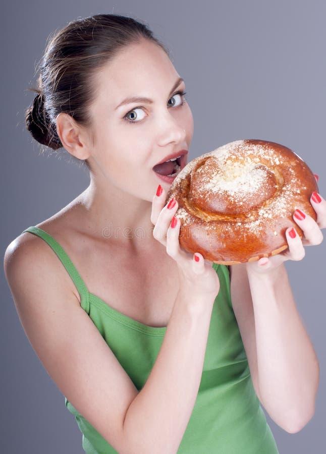 Jongelui die mooi vrouw het bijten broodje glimlachen stock foto