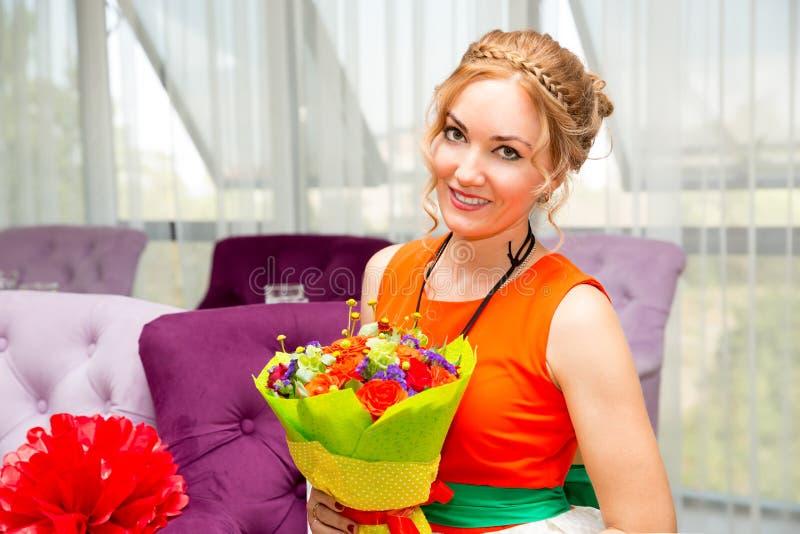 Jongelui die mooie vrouw met een boeket van bloemen glimlachen bij de verjaardag Portret in een koffie stock foto