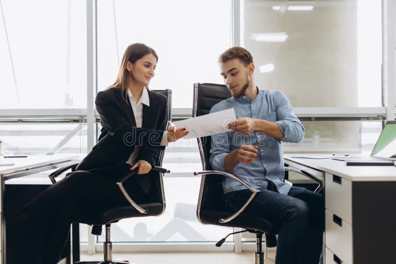 Jongelui die persoonlijk hulp gevend document glimlachen aan beambte in zijn bureau, vrouwelijke accountant die het grote werk me royalty-vrije stock foto's