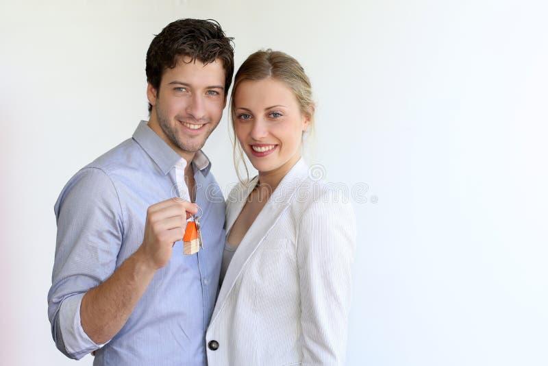 Jongelui die slimme paar geïsoleerde holdingssleutels glimlachen stock fotografie