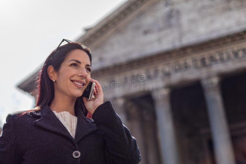 Jongelui die uitvoerende vrouwenbesprekingen charmeren door een mobiele pho van de telefooncel royalty-vrije stock afbeeldingen