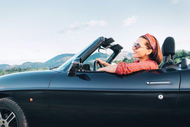 Jongelui die vrolijk wijfje glimlachen die retro stijl convertibele auto drijven in zonnige dagtijd royalty-vrije stock fotografie