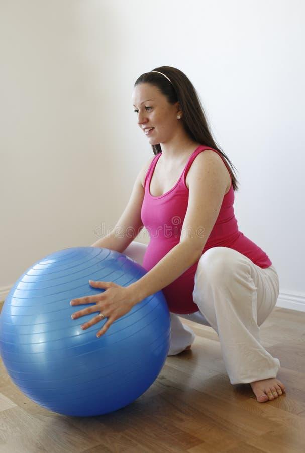 Jongelui die zwangere vrouw glimlachen die het hurken oefening doet royalty-vrije stock afbeelding