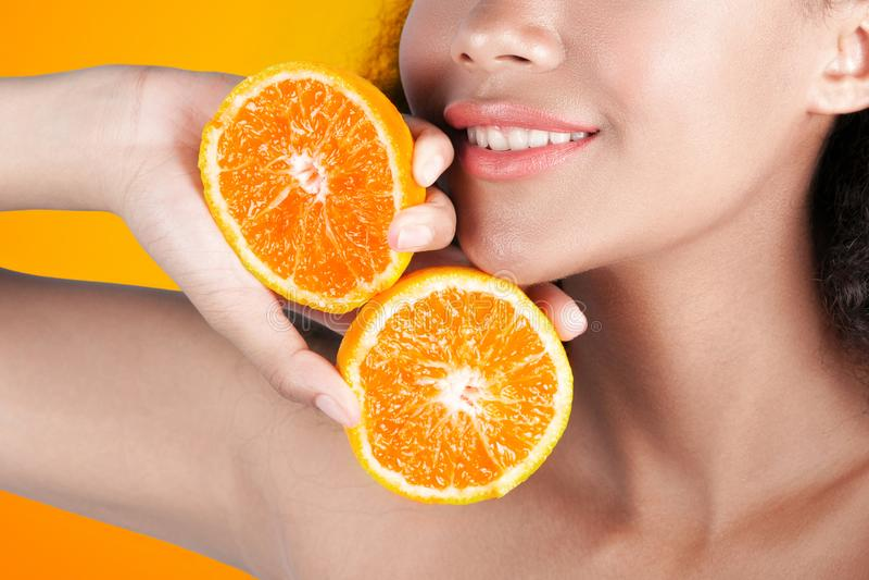 Jongelui die zwart meisje met schone perfecte huid met oranje close-up glimlachen stock foto