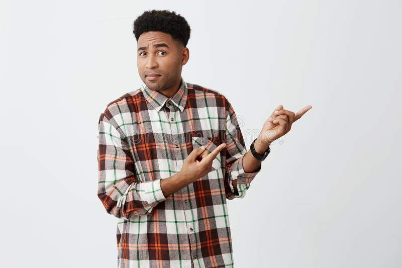 Jongelui donker-gevilde Afrikaanse aantrekkelijke mannelijke student met modieus krullend kapsel die in toevallig geruit overhemd stock fotografie