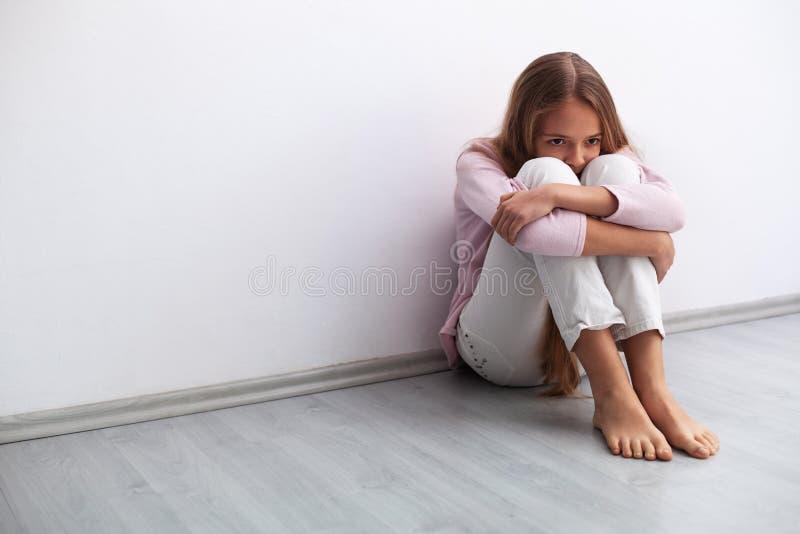 Jongelui of droevige meisjeszitting op de vloer door de muur ongerust die worden gemaakt die royalty-vrije stock afbeelding