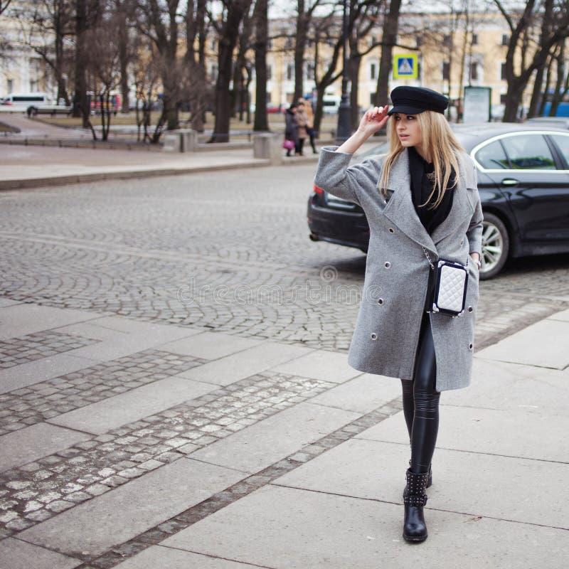 Jongelui, heup en aantrekkelijk blonde rond de stad lopen, meisje in een modieuze hoed en een grijze laag die royalty-vrije stock afbeeldingen