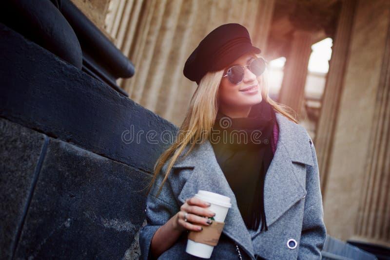Jongelui, heup en aantrekkelijk blonde rond de stad met koffie lopen om te gaan, meisje in een modieuze hoed en een grijze laag d royalty-vrije stock fotografie