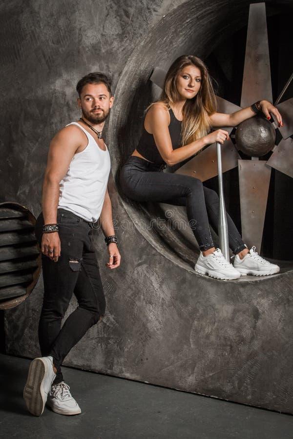 Jongelui koppelt een man en een vrouw met een speelse stemming, modieus en sportief kijkt zit dichtbij een industriële ventilator royalty-vrije stock fotografie