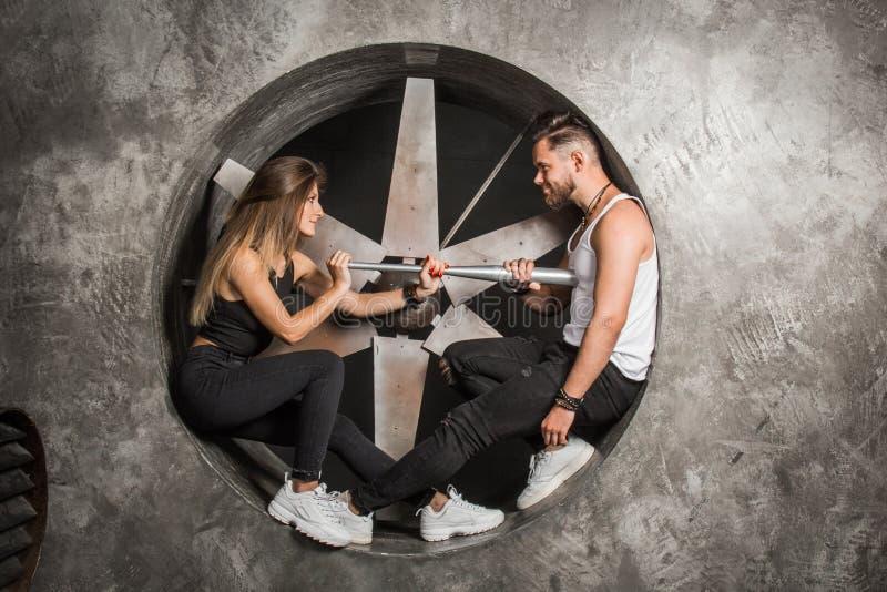 Jongelui koppelt een man en een vrouw met een speelse stemming, modieus en sportief kijkt zit dichtbij een industriële ventilator stock fotografie