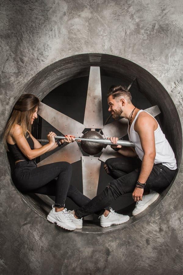 Jongelui koppelt een man en een vrouw met een speelse stemming, modieus en sportief kijkt zit dichtbij een industriële ventilator royalty-vrije stock afbeelding