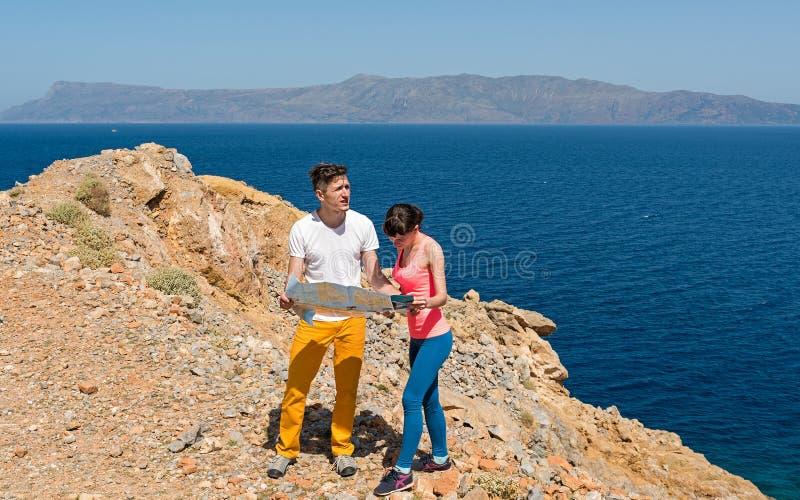 Jongelui koppelt het bekijken de kaart dichtbij het overzees stock foto