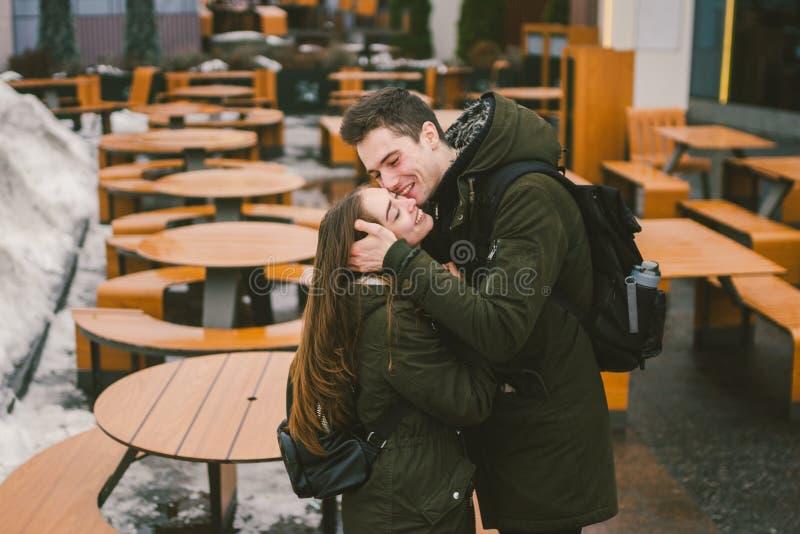 Jongelui koppelt in liefde en een meisje en een student bevinden zich omhelzend dichtbij de lijsten van een gesloten koffie van h royalty-vrije stock afbeelding