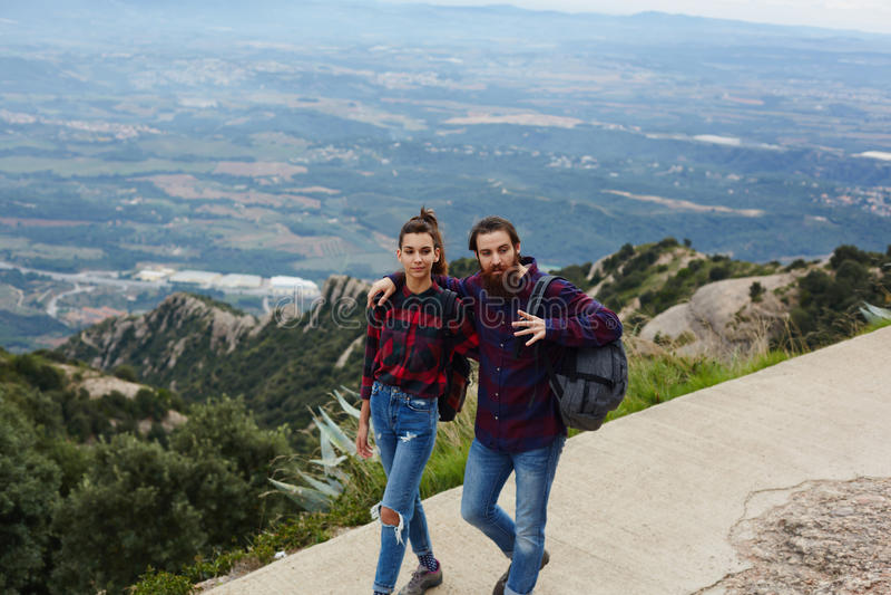 Jongelui koppelt reizigers die neer uit de bergman omhelzend komen zijn geliefd stock fotografie