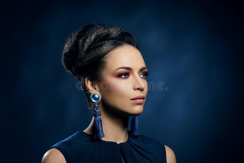 Jongelui, mooi en rijke vrouw in juwelen van platina en stenen over luxeachtergrond stock afbeeldingen