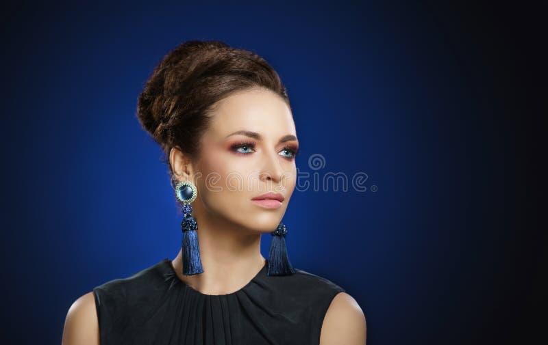 Jongelui, mooi en rijke vrouw in juwelen van platina en stenen over luxeachtergrond stock afbeelding