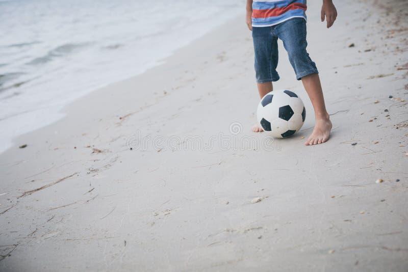 Jongelui weinig jongen die op het strand met voetbalbal spelen stock afbeelding
