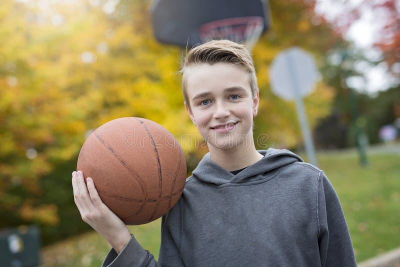 Jongen alleen tijdens basketbalspel buiten royalty-vrije stock afbeelding