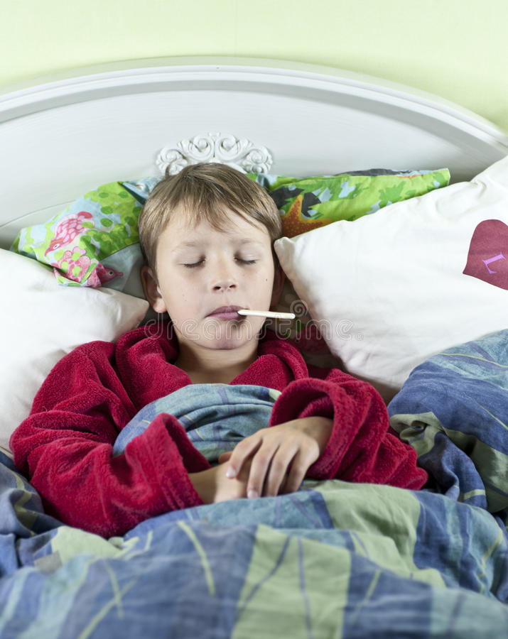Jongen in bed met koorts stock afbeelding