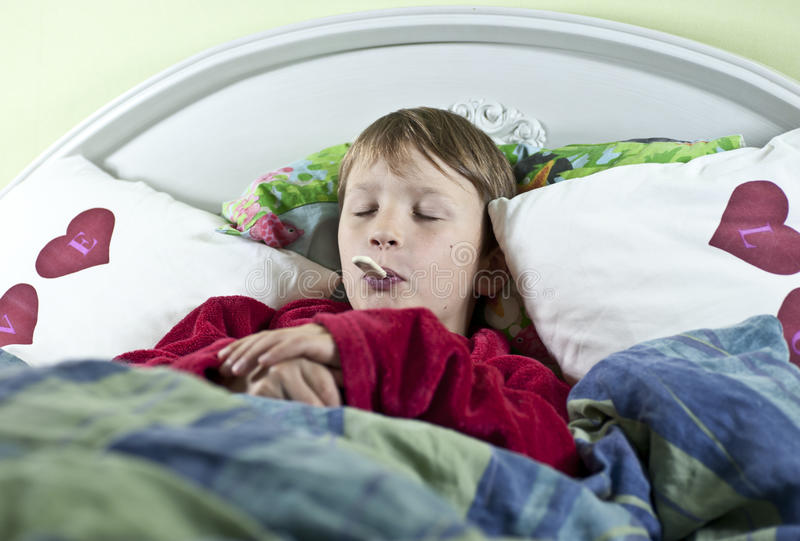 Jongen in bed met thermometer stock afbeeldingen