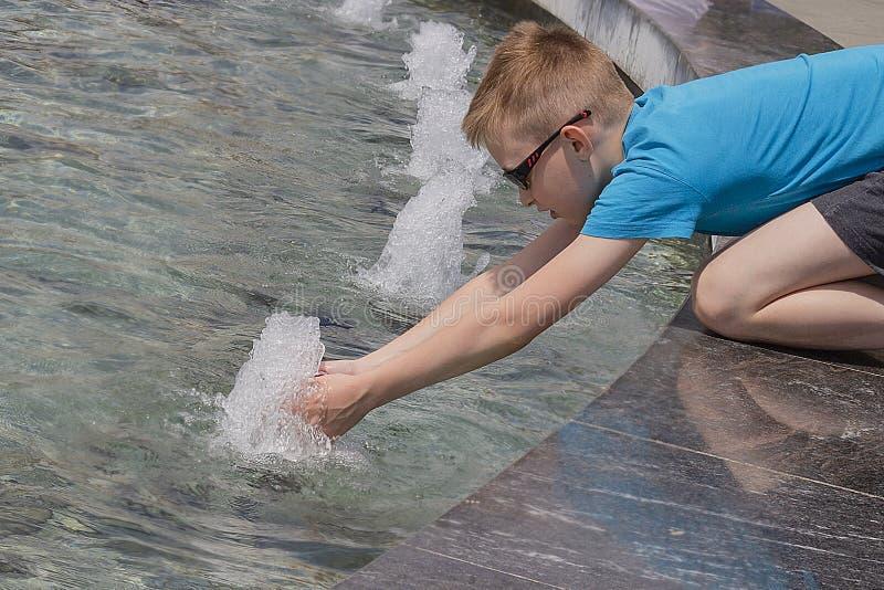 Jongen bij de fontein in de stad in heet weer royalty-vrije stock fotografie