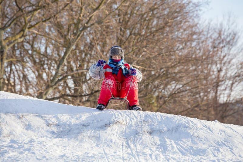 Jongen bij de slee bovenop sneeuwheuvel die op het berijden wachten stock foto's