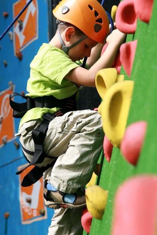 Jongen bij het beklimmen van muur stock foto