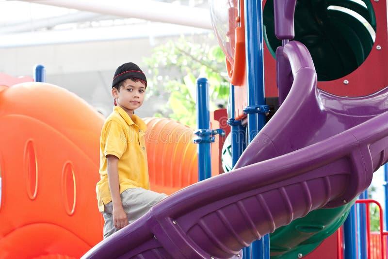 Jongen bij kleurrijke openluchtspeelplaats stock afbeelding