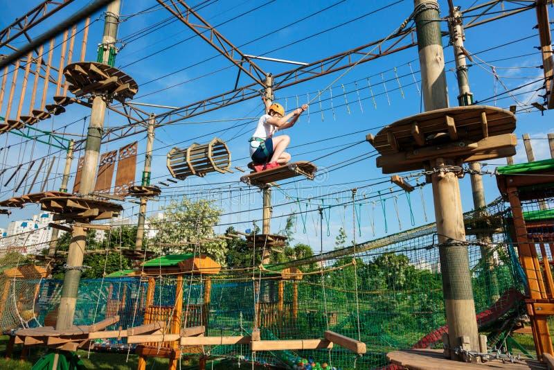Jongen in bosavonturenpark Het jonge geitje in oranje helm en witte t-shirt beklimt op hoge kabelsleep Openlucht beklimmen royalty-vrije stock afbeelding
