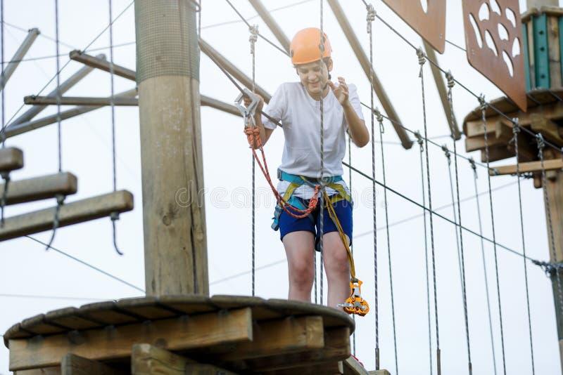Jongen in bosavonturenpark Het jonge geitje in oranje helm en witte t-shirt beklimt op hoge kabelsleep Openlucht beklimmen, verma royalty-vrije stock afbeelding