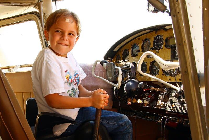 Jongen in cockpit van privé vliegtuig royalty-vrije stock afbeelding