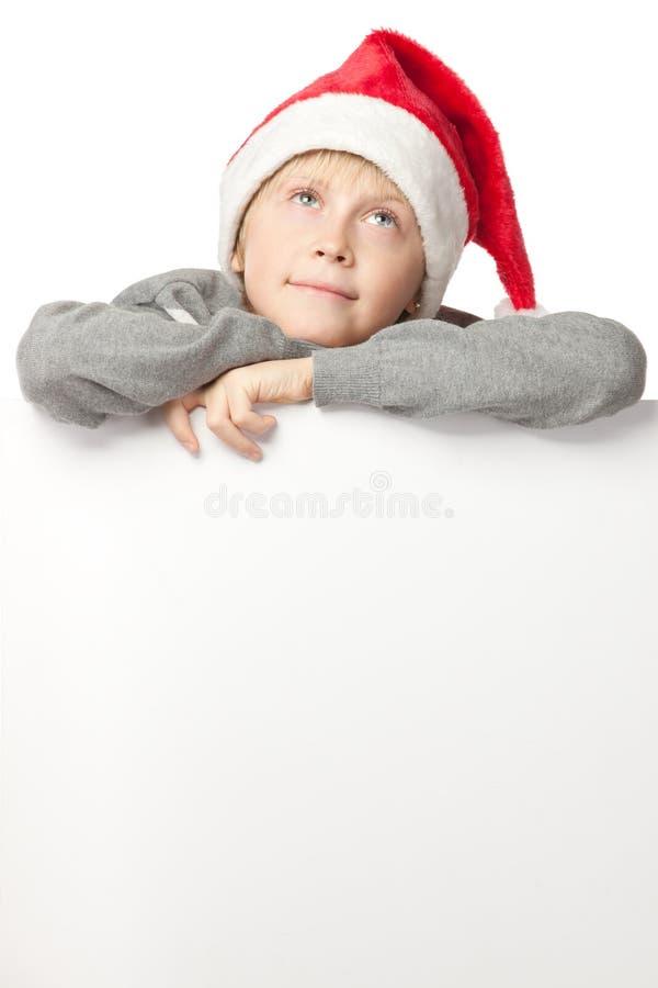 Jongen in de hoed van de Kerstman met lege raad royalty-vrije stock afbeelding
