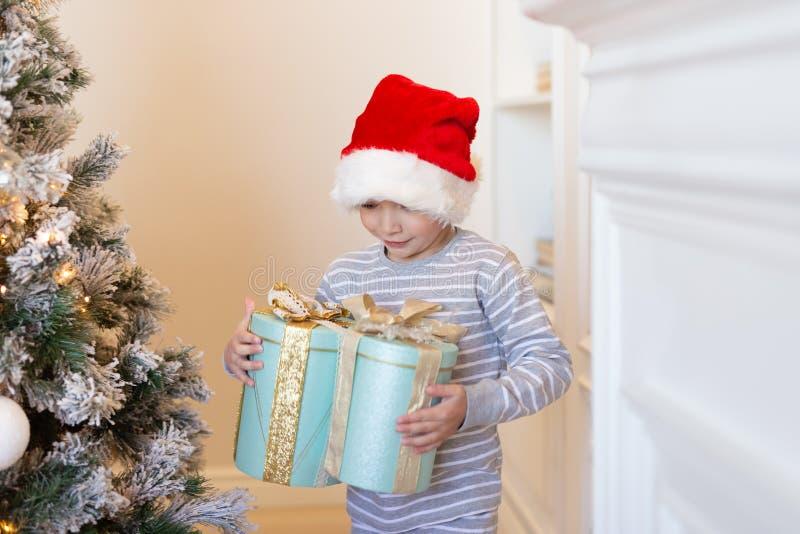 Jongen in de holdingsgiften van de santahoed dichtbij Kerstmisboom De decoratie van Kerstmis Nieuw jaar en Kerstmisconcept Magisc royalty-vrije stock afbeeldingen