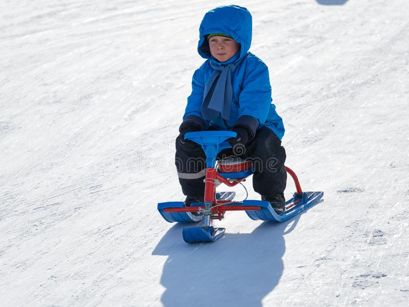 Jongen in de ritten van de de winterslee op de berg stock afbeelding