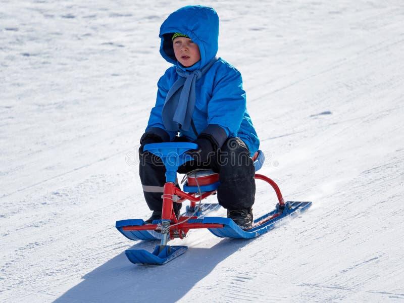 Jongen in de ritten van de de winterslee op de berg royalty-vrije stock afbeelding