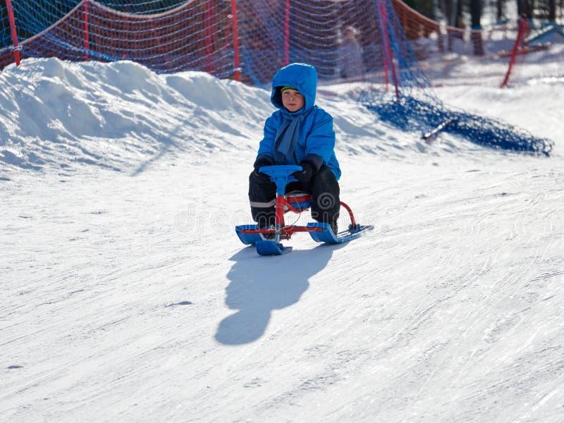 Jongen in de ritten van de de winterslee op de berg royalty-vrije stock fotografie