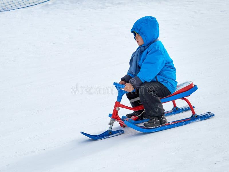 Jongen in de ritten van de de winterslee op de berg stock foto