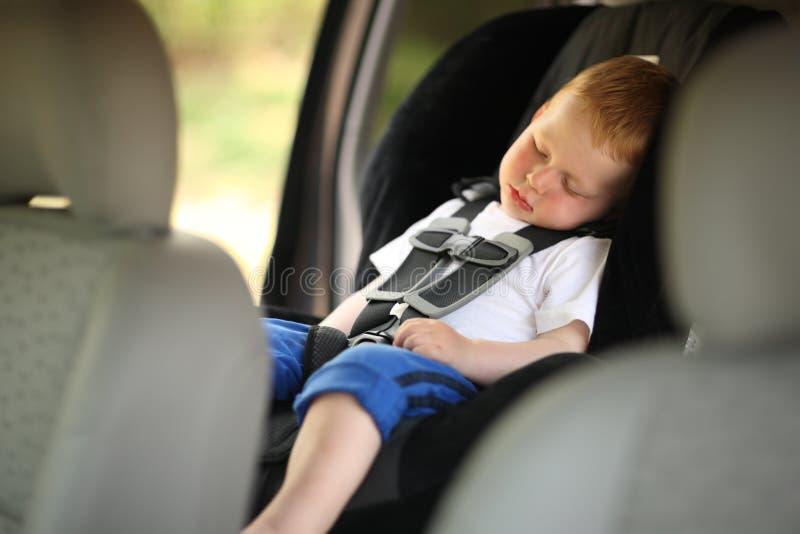 Jongen in de zetel van de kindauto stock foto's
