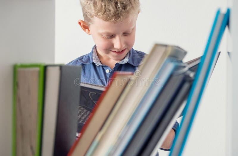Jongen dichtbij boekenrek gelezen interessant boek royalty-vrije stock afbeelding