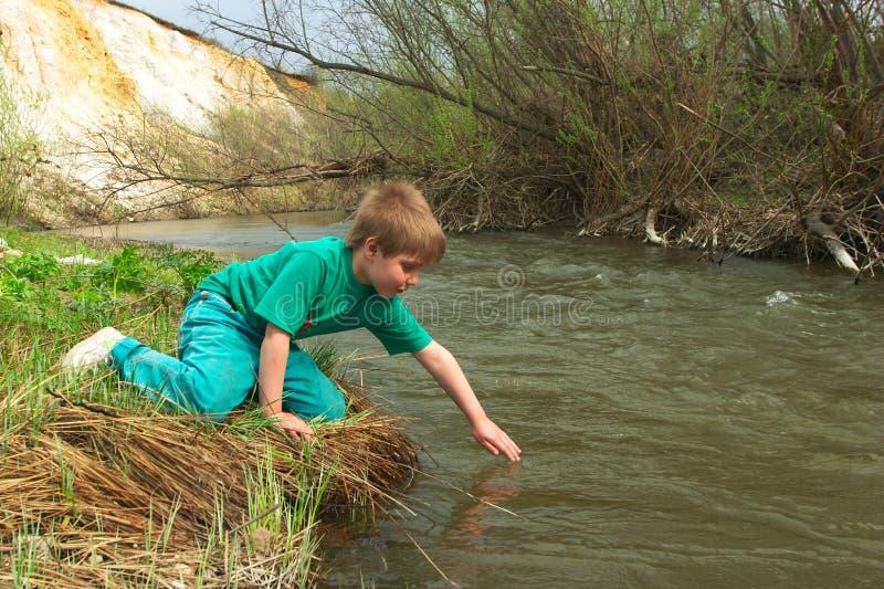 Jongen dichtbij de rivier royalty-vrije stock foto